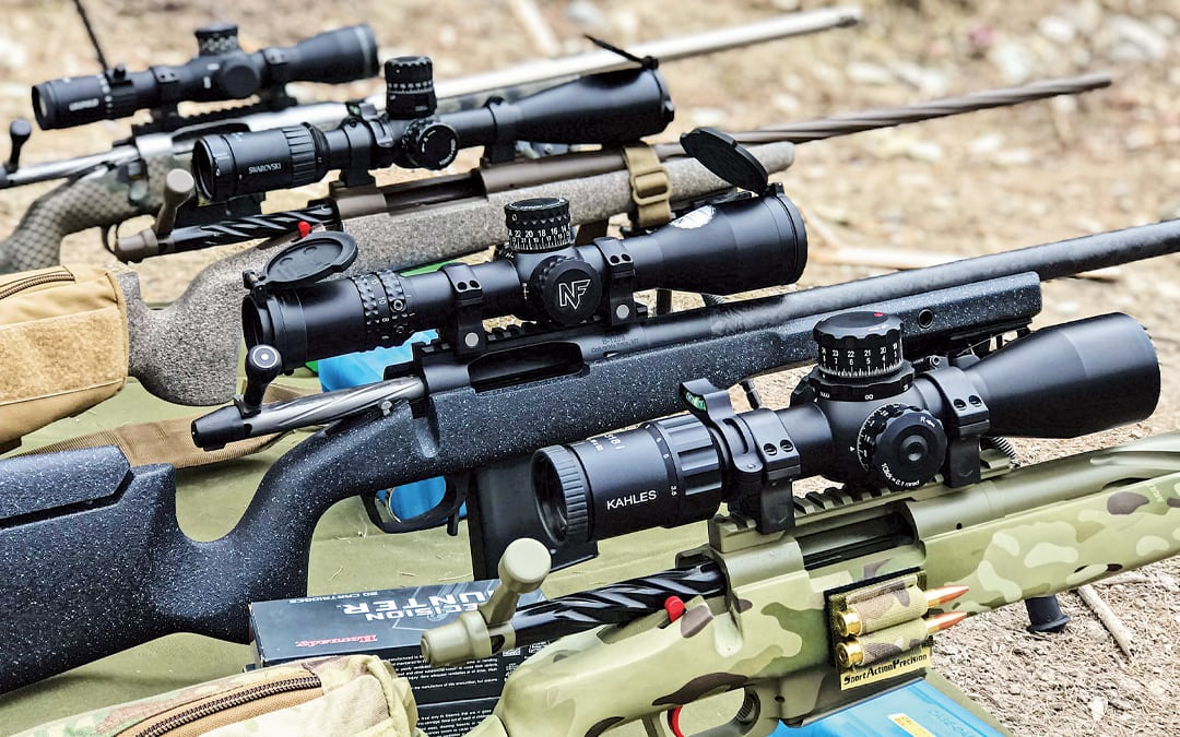 Four scopes mounted to rifles